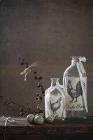 Decorated glass bottles and quail eggs on wooden table in front of grey wall