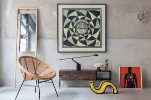 Low sideboard below framed geometric picture on vintage-effect wall and mirror on stand to one side