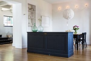 Old panelled sideboard used as partition in front of dining table