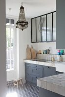Vintage-style kitchen with grey cabinets and chandelier