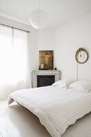 White bedroom with corner fireplace and floating bed