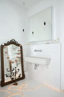 Light rope on floor next to antique mirror leant against wall in bathroom