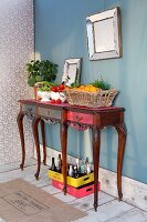 Renovated, antique console table with drawers decorated with vegetables and fruit basket