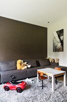 Toys, grey sofa and wall with structured surface in living room