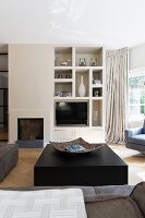 Solid black block as coffee table in front of fireplace and masonry shelves