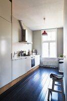 Schlichte Küche mit schwarzem Dielenboden