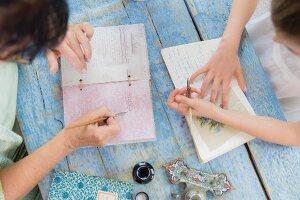 Zwei Personen sitzen am Holztisch und schreiben in ein Poesiealbum
