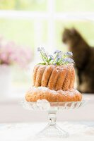 Forget-me-nots in bundt cake on glass cake stand