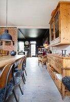 View past old wooden furniture in dining room into black kitchen