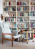 Sessel mit Karobezug und runder Beistelltisch vor dem Bücherregal
