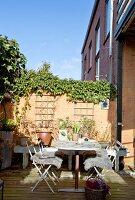 Gemütlicher Sitzplatz auf der Terrasse mit bewachsener Mauer
