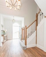 A staircase with a grey carpet in an elegant entrance with an open front door