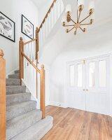 Treppenaufgang mit grauem Treppenteppich in Diele vor weisser Flügeltür