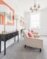 An elegant salon with two black console tables and table lamps in front of framed pictures