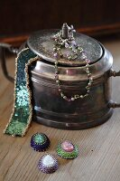 Vintage silver pot decorated with glass-bead jewellery and three necklace pendants