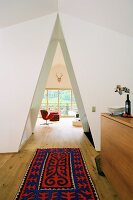Brightly patterned rug in front of triangular open doorway