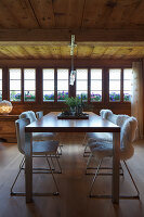 Modern dining table and white chairs in dining room with long bank of windows