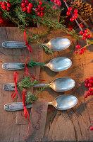 Silberlöffelchen, dekoriert mit Wacholderzweig und rotem Band zu Weihnachten