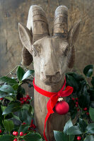 Wooden ibex decorated with wreath of holly, ribbon and bauble