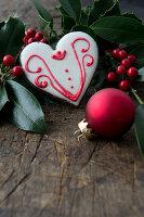 Herzplätzchen mit Zuckerguss, Ilex und Christbaumkugel