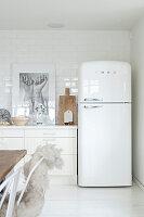 Retro fridge in white kitchen with wooden accessories