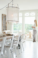 Woman looking out of window in dining room with white floor