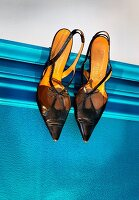 Shoes hung from picture rail on blue wall