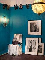 Grossformatige schwarz-weisse Fotos, Hussenstuhl, Wandleuchte und Kronleuchter in Garderobe mit blauer Wand als Schuhregal