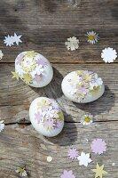 Mit ausgestanzten Blümchen verzierte Eier auf Holzbrettern
