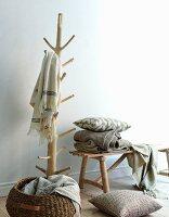 Decken und Kissen in Naturfarben auf Garderobenständer und Bank aus Treibholz