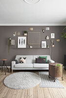 Pictures and ornaments on grey wall above sofa