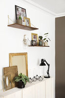 Wall-mounted shelves above sideboard and pictures with backs turned to room