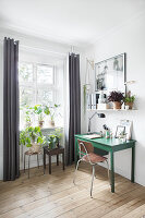 Green desk, retro chair and house plants in work area