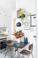 Small dining area in kitchen with vase of flowers on table and decorated wall