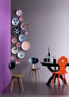 Vertical arrangement of designer wall plates on grey wall, designer chair and black round table