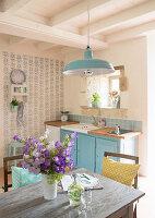 Tisch mit Blumenstrauss in Landhausküche