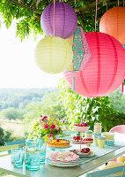 Lampions über gedecktem Gartentisch