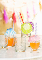 Drinks in glasses with straws and drinks covers made from paper cake cases