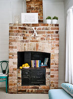 Vintage ornaments on black range stove in brick fireplace