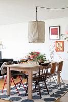 Dining table and various chairs on spotted rug