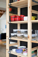 Crockery and storage containers on simple wooden shelves