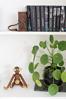 Wooden monkey next to houseplant on bookshelves