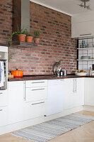 Brick wall in white kitchen