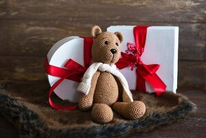 Knitted teddy bear in front of Christmas presents