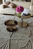 Two round shiny side tables on rug with floral relief pattern
