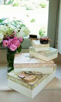 Stacked vintage boxes, shoe polish, shoe horn and vase of flowers on windowsill