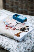 Scissors, tassel and ribbons on folded fabric