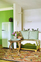 Green bench with animal-skin rug and round table next to partition with fridge on other side