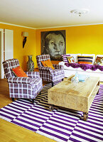 Rustic wooden coffee table, tartan armchairs and purple and white striped rug in living room with yellow walls