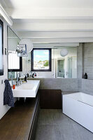 Mirrored wall in bathroom with low sideboard along one wall